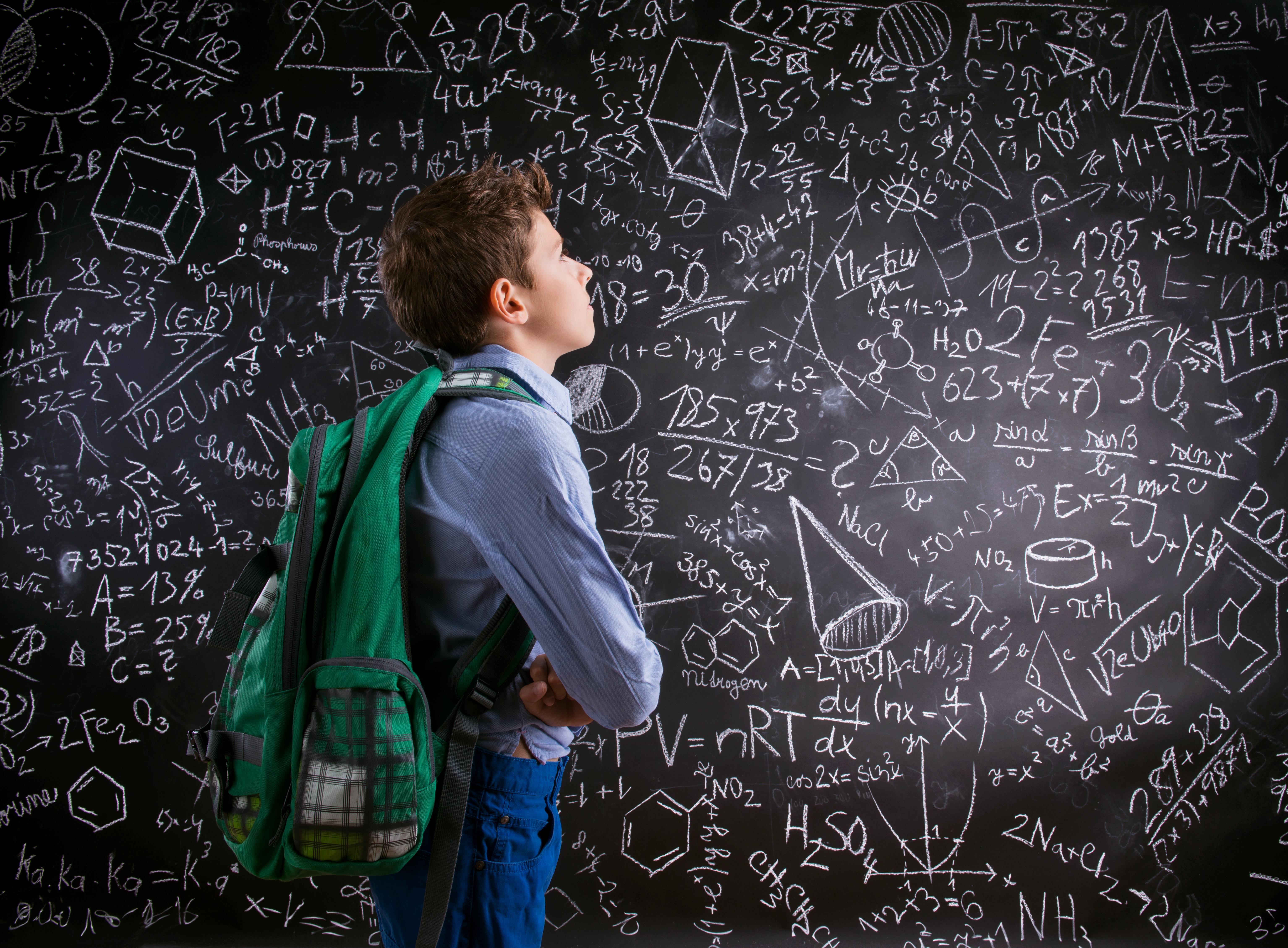 Boy  with schoolbag against big blackboard with mathematical sym