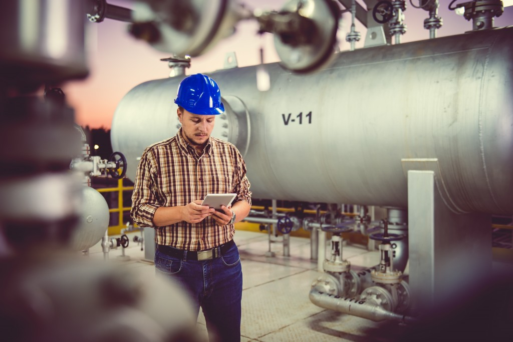 Man using tablet at Natural gas processing facility