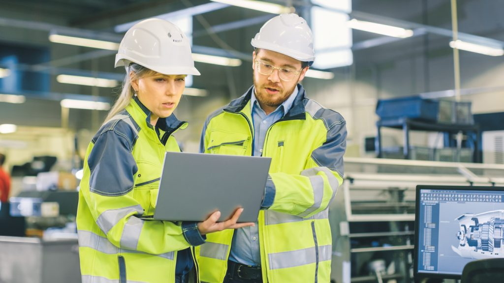 Male Industrial Worker and Female Chief Mechanical Engineer in Walk Through Manufacturing Plant while Discuss Factory's New Project and Using Laptop. Facility Has Working Machinery.