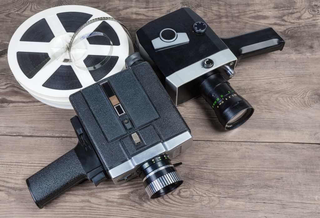 Two old vintage amateur film movie cameras powered by clockwork motor and electric motor and reels of motion picture films Super 8mm format on an old wooden surface