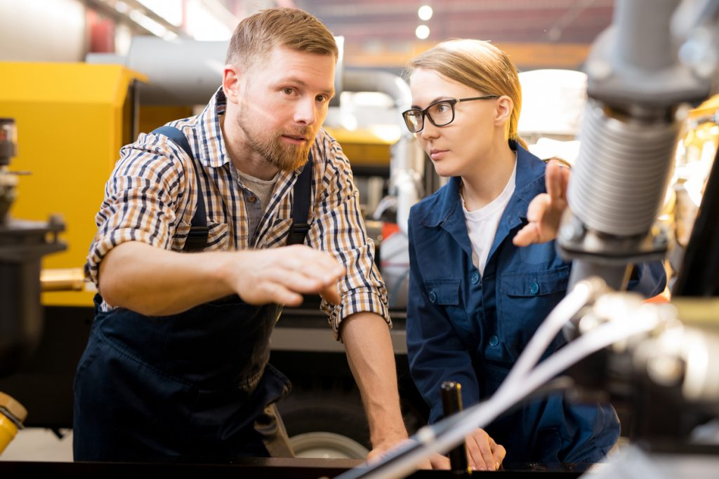 One of young confident technicians pointing at mechanism of industrial equipment during discussion of its qualities with colleague (One of young confident technicians pointing at mechanism of industrial equipment during discussion of its qualities wit