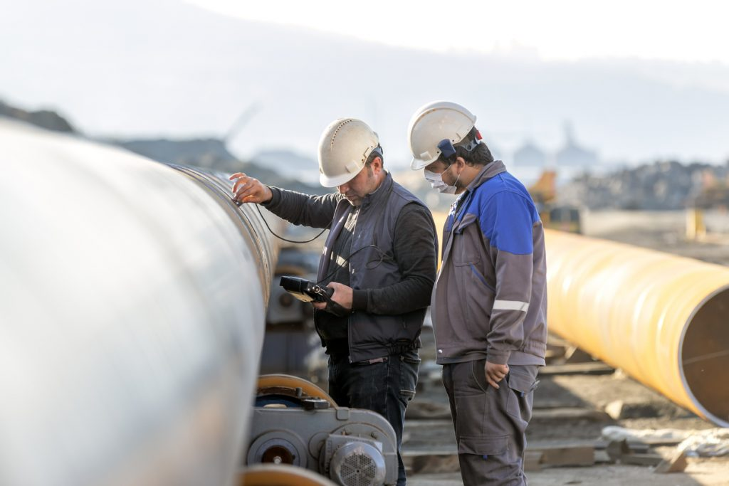 Non-destructive testing technicians are checking welds of pipe with ultrasonic testing (UT) method. Ultrasonic testing is often performed on steel and other metals and alloys.